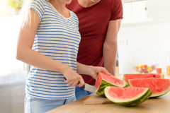 Young couple in a kitchen slicing red watermelon. Couple in their contemporary white kitchen Royalty Free Stock Image
