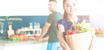 Young couple in the kitchen , woman with a bag of groceries shopping Stock Images