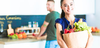 Young couple in the kitchen , woman with a bag of groceries shopping Stock Photography