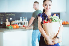 Young couple in the kitchen , woman with a bag of groceries shopping Royalty Free Stock Photo