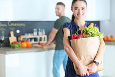 Young couple in the kitchen , woman with a bag of groceries shopping Royalty Free Stock Images