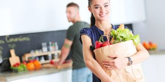 Young couple in the kitchen , woman with a bag of groceries shopping Royalty Free Stock Photos