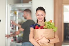 Young couple in the kitchen , woman with a bag of groceries shopping Stock Photos