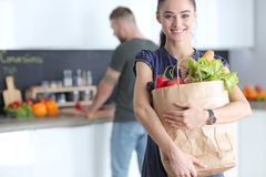 Young couple in the kitchen , woman with a bag of groceries shopping. Young couple in the kitchen , women with a bag of groceries shopping royalty free stock photography