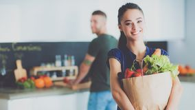 Young couple in the kitchen , woman with a bag of groceries shopping. Young couple in the kitchen , women with a bag of groceries shopping stock photo