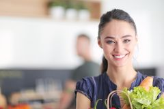 Young couple in the kitchen , woman with a bag of groceries shopping Royalty Free Stock Image