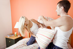 Young Couple Kneeling on Bed Having a Pillow Fight. Young couple facing each other, kneeling on bed having a pillow fight. Horizontal shot Stock Photo
