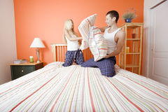 Young Couple Kneeling on Bed Having a Pillow Fight Stock Image