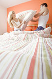 Young Couple Kneeling on Bed Having a Pillow Fight Stock Images
