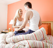 Young Couple Kneeling on Bed Smiling Royalty Free Stock Image