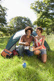 Young couple kneeling beside dome tent in woodland clearing, taking boiled kettle from camping stove, smiling, portrait Royalty Free Stock Images