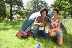 Young couple kneeling beside dome tent in woodland clearing, taking boiled kettle from camping stove, smiling, portrait Stock Photography