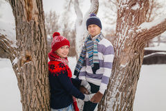 Young couple in knitted clothing in winter Park. Winter love story. Stock Photos