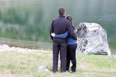 Young Couple by a Lake. Young romantic couple of hikers in sport suits hugging and enjoying the view of a lake Royalty Free Stock Photos
