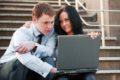 Young couple with laptop. On the steps Stock Images