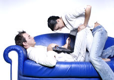 Young couple with laptop. Young couple sitting in a sofa using a laptop Royalty Free Stock Photos