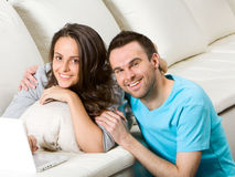 Young couple with laptop. On white sofa Royalty Free Stock Photos
