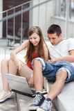 Young couple with laptop. Portrait of young couple outdoors Stock Photos