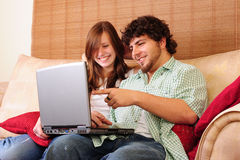 Young couple with laptop. Young couple sitting on a couch pointing and having fun with a laptop computer royalty free stock photos