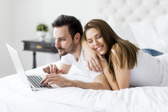 Young couple with laptop in the bed. Young couple with a laptop in the bed Stock Images