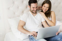 Young couple with laptop. In the bed Royalty Free Stock Photography