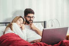 Young couple with laptop in the bed. In room Stock Image
