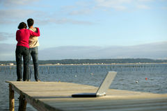 Young couple with laptop computer on a dock. Young couple standing on a pontoon looking at the view, from behind, laptop in the foreground Royalty Free Stock Photo