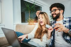 Young couple with laptop and credit card at home. Internet shopping concept Royalty Free Stock Photography