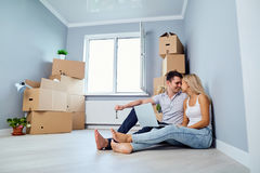 Young couple with laptop on the floor in a new house. Housewarming Stock Image