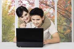 Young couple with laptop at home Stock Images