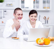 Young couple with laptop in the kitchen Stock Photo