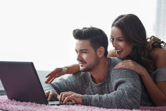 Young couple with laptop lying prone on carpet Royalty Free Stock Images