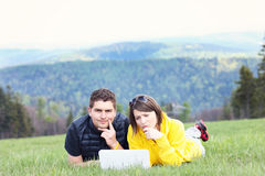 Young couple and laptop in the mountains stock images