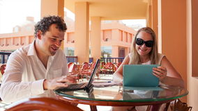 Young couple with laptop and pad. Young couple on a cafe terrace. Man working with laptop and woman using touchpad stock footage