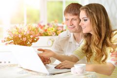 Young couple with laptop. Portrait of happy young couple with laptop at home Stock Photos