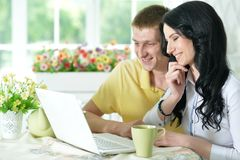 Young couple with laptop. Portrait of happy young couple with laptop at home Stock Images