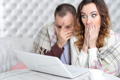 Young couple with laptop. Portrait of shocked young couple with laptop at home Royalty Free Stock Images