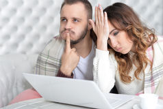 Young couple with laptop. Portrait of stressed young couple with laptop at home Stock Photos