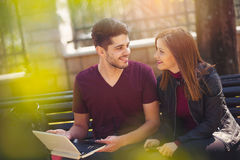 Young couple with laptop sitting on bench outdoor websurfing Royalty Free Stock Photos