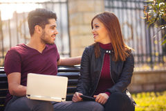 Young couple with laptop sitting on bench outdoor websurfing Royalty Free Stock Photo