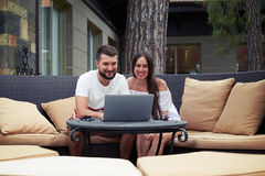 Young couple with laptop on terrace in yard Stock Image