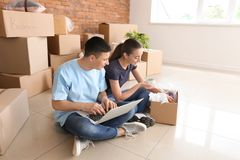 Young couple with laptop unpacking box indoors. Moving into new house stock image
