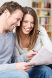 Young couple laughing as they discuss paperwork Royalty Free Stock Photos