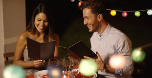 Young couple laughing as they go through the menu. At a restaurant ordering their meal with colorful party lights behind them Stock Images