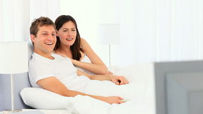 Young couple laughing in front of tv Stock Photos