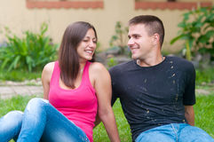 Young couple laughing having fun while sitting in garden Royalty Free Stock Image