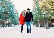 Young couple laughing having fun while walking in snowy winter park. Together enjoying good weather stock photography