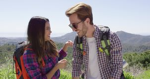 Young couple laughing while hiking. Young smiling couple posing while hiking in mountains and looking away with landscape on background stock footage