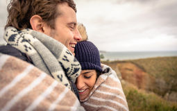 Young couple laughing outdoors under blanket in a Royalty Free Stock Images
