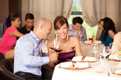 Young couple laughing  restaurant. Young couple sitting at the restaurant table, joking over a glass of wine Royalty Free Stock Photo